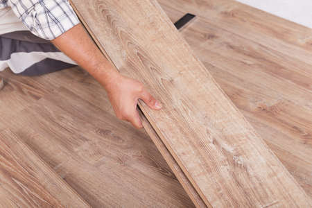 Installing laminate flooring. Carpenter lining parquet boards to each other fitting a plank Stockfoto