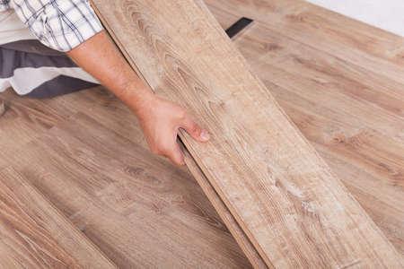 Het installeren van laminaatvloer. Carpenter voering parket planken aan elkaar monteren van een plank