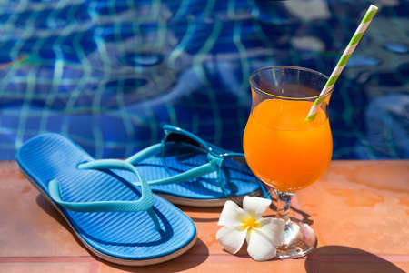 Orange mango fresh juice smoothie drink cocktail slippers and sunglasses near swimming pool - summer holiday concept
