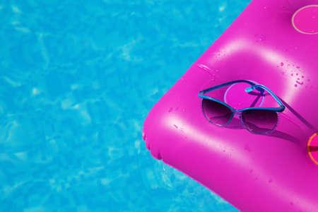 Occhiali da sole su un materasso ad aria rosa in piscina. concetto di estate tropicale.
