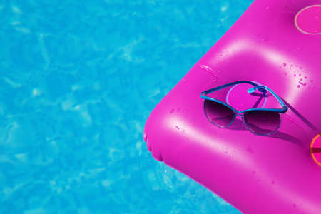 Sunglasses on a pink air mattress in swimming pool. Tropical summer concept.