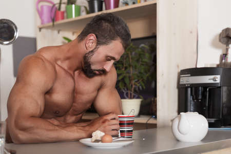 Muscle shirtless bachelor man have a breakfast in the kitchen