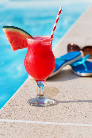red straw: Water melon red fresh juice smoothie drink cocktail slippers and sunglasses near swimming pool Stock Photo