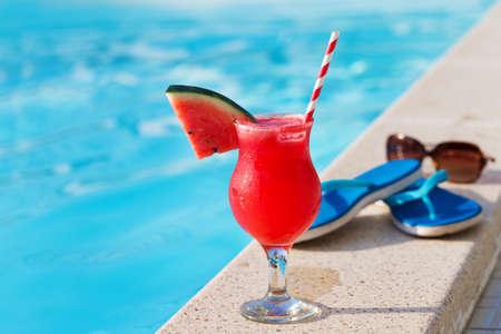 水メロン赤のフレッシュ ジュース スムージー飲むカクテル スリッパとスイミング プール付近にサングラス