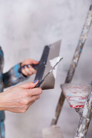 stucco house: house improvement by woman worker puts finishing layer of stucco on the wall using a plastering trowel