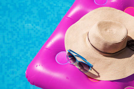 Sunglasses and straw hat on a pink air mattress in swimming pool. Tropical summer concept. Stock Photo