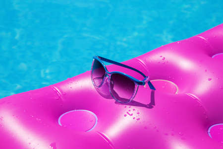 lilo: Sunglasses with pink mattress at the swimming pool - holiday tropical concept