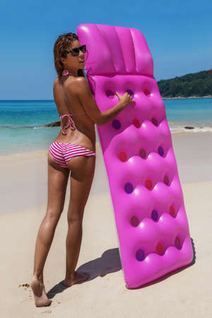 Young slim brunette woman in sunglasses gets suntan with an air mattress on the tropic beach