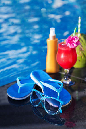 Water-melon  fresh fruit smothie drink with sunglasses, sunscreen creame, slippers and coconut on the swimming pool border - holiday tropical concept