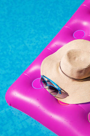 lilo: Sunglasses and straw hat on a pink air mattress in swimming pool. Tropical summer concept. Stock Photo