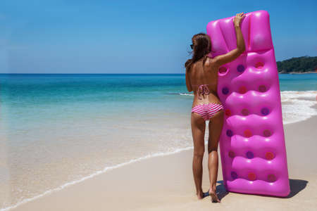 colorfully: Young slim brunette woman in sunglasses sunbathe with an air mattress on the tropic beach