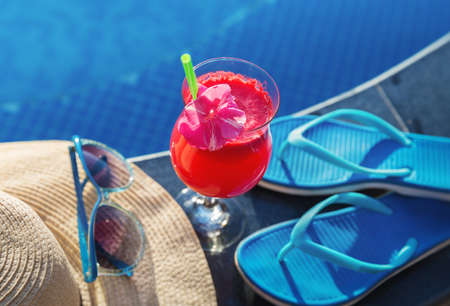 Watermelon fresh juice smoothie drink glass with flower, sunglasses near swimming pool Stock Photo