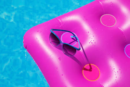 Sunglasses with pink mattress at the swimming pool - holiday tropical concept