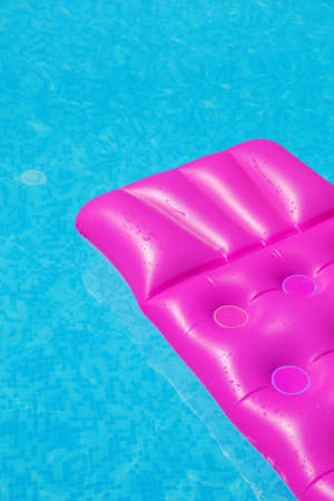 lilo: Pink air mattress on a swimming pool - holiday tropical background concept
