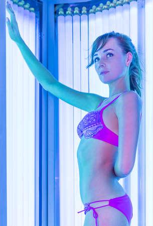 solarium: Pretty slim woman getting sun tan in a solarium