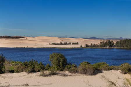 ne: White sand dunes with the lake and trees at the Mui Ne village Vietnam