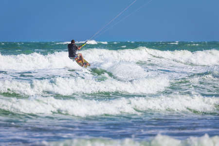 ne: Athletic man riding on kite surf board on a sea waves