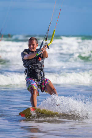 kiteboarding: Athletic man riding on kite surf board on a sea waves