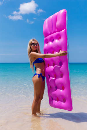 colorfully: Slim blonde woman with air mattress on a tropic beach