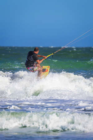 man flying: Young atletic man riding kite surf on a sea in Vietnam