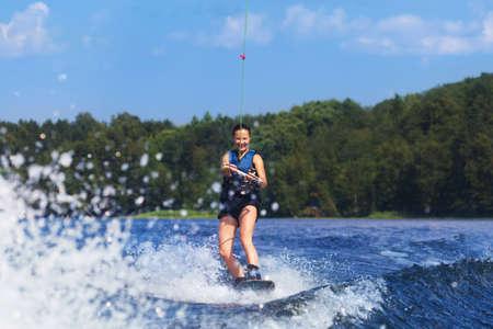 夏の湖でモーター ボートの波でウェイク ボードに乗って若いかなりスリム ブルネットの女性 写真素材
