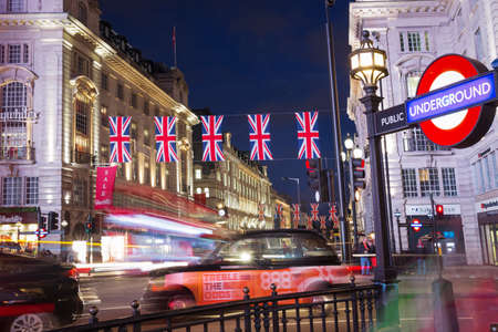 Popular tourist Picadilly circus with flags union jack in night lights illumination in London, England, United Kingdom Editorial