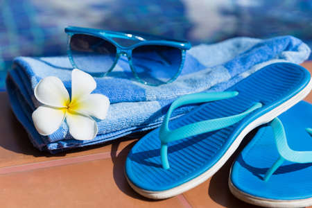 Blue slippers, sunglasses and towel on border of a swimming pool - holiday tropical concept Imagens