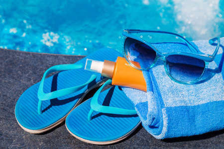 Sunglasses with sunscreen cream, blue slippers and towel on border of a swimming pool - holiday tropical concept