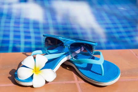 Blue slippers and sunglasses on border of a swimming pool - holiday tropical concept Stock Photo