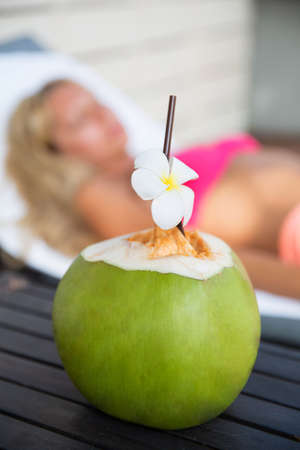 Coconut juice drink with woman on lounger near a swimming pool - holiday tropical concept