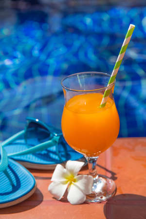 Glass of orange juice drink fresh with flowers, sunglasses and slippers on border of a swimming pool - holiday tropical concept
