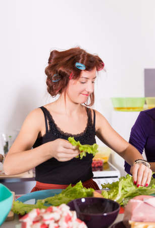Young pretty woman housewife cooking with curlers on hair Reklamní fotografie