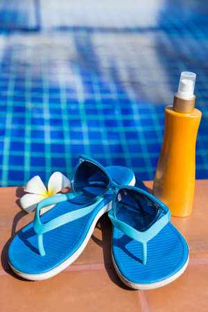 Blue slippers with sunscreen cream and sunglasses on border of a swimming pool - holiday tropical concept