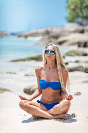 Young pretty blond woman in blue bikini on a white tropic beach Standard-Bild