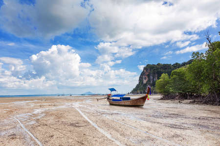traditional longtail boats, rocks, cliffs, beautiful sea tropical and white East Railay beach low tide water. Popular famous travel vacation destination Krabi Province, Thailand. Stock Photo
