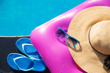 Blue slippers, sunglasses, straw hat and pink air mattress on border of a swimming pool - holiday tropical concept