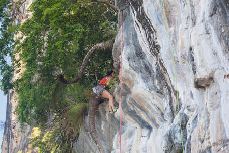 Young slim athletic woman climbing on a white karst rock mountain in Thailand Archivio Fotografico