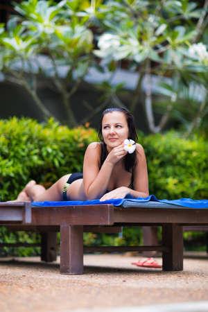 Young woman gets suntan near tropical swimming pool in black bikini Stock Photo