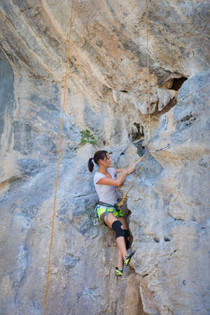 Young woman rock climbing on white mountain  in Thailand