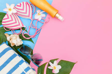 Tropical top view summer holiday concept still life with monstera liana, vine, palm leaves on pink and blue background flat lay layout