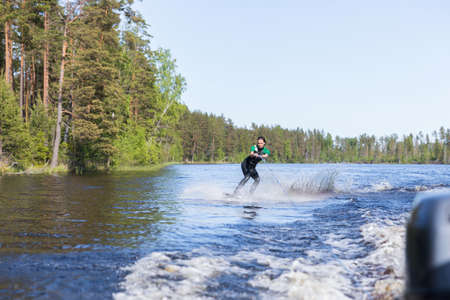 Young pretty slim brunette woman in wetsuit riding wakeboard on wave of motorboat in a summer lake
