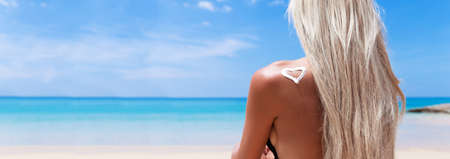 Young pretty slim blonde woman with sunscreen cream in heart shape on a shoulder on the beach Stock Photo