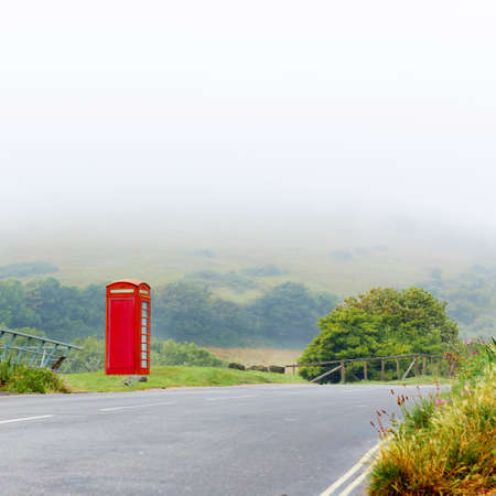 Fog with classical red telephone booth box in misty English countryside, United Kingdom