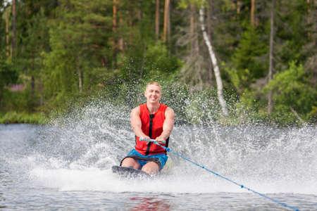 Junger athletischer Mann, der Kniebrett auf einem See reitet
