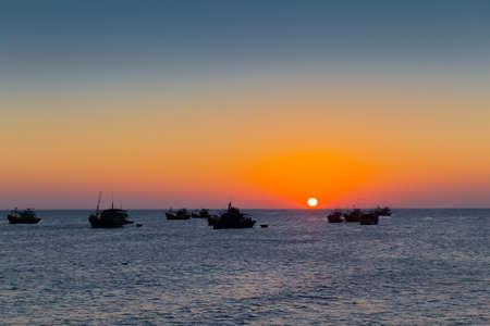 Vietnam Mui Ne village fishing boats and ships in evening sunset light 版權商用圖片