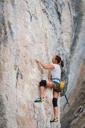 Young woman rock climbing on a karst limestone white mountain in Thailand