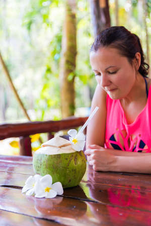 Fresh coconut cuts with tropical palm leaves and white frangipani flowers in front of woman in tropical bar