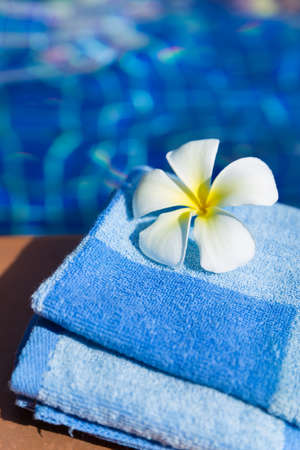 Fluffy blue towel with plumeria frangipani flower on border of a swimming pool - holiday tropical concept