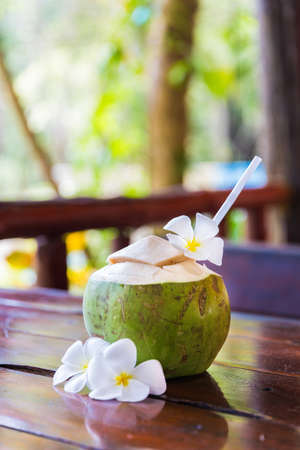 Fresh coconut cuts with tropical palm leaves and white frangipani flowers with straw