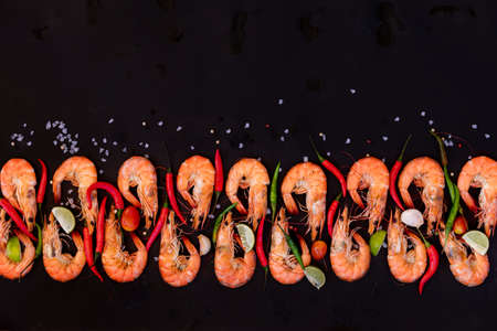 Perfect cooked prawns shrimps with herbs, spices and text space note book top view flat lay